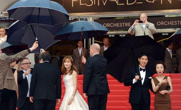 영화 '다른 나라에서'로 제65회 칸영화제에 참석했던 윤여정. 레드 카펫 위에서 유준상과 함께 사진을 찍기 위해 멈춰 서 있고, 그들의 왼편으로 함께 영화를 찍은 프랑스 국민 배우...