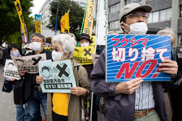 Demonstrators hold slogans during a protest against the Japanese governments plan to release more than...