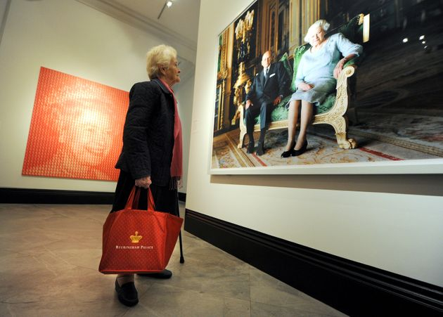 A woman views a photograph titled Queen Elizabeth II and The Duke of Edinburgh, Windsor Castle 2011 by...
