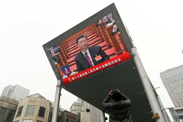 A man uses his mobile phone to take a picture of a big screen showing China's President Xi Jinping attending...