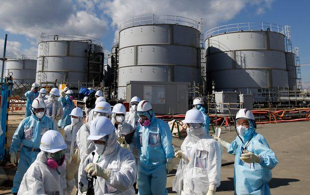 Des employés de TEPCO devant des citernes d'eau radioactive sur le site de