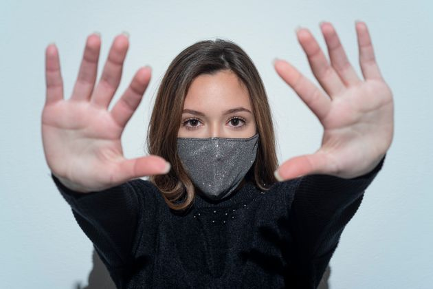 Portrait of worry young woman wearing face mask and showing stop gesture.studio shot.