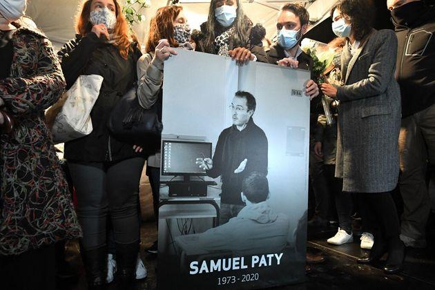 Des proches de Samuel Paty tenant une pancarte à son effigie lors d'une marche blanche à Conflans-Sainte-Honorine,...