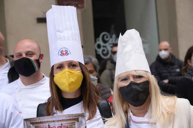 FLORENCE, ITALY - APRIL 13: women wearing face masks and chef's hats protest against the closure of restaurants...