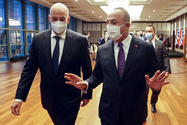 Turkish Foreign Minister Mevlut Cavusoglu (R) speaks with Greek Foreign Minister Nikos Dendias as they arrive to the press conference following their meeting in Ankara on April 15, 2021. (Photo by Adem ALTAN / AFP) (Photo by ADEM ALTAN/AFP via Getty Images)