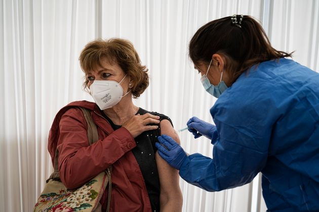 A nurse administers the AstraZeneca vaccine against Covid-19 to a woman at Casal de Gent Gran Quatre...