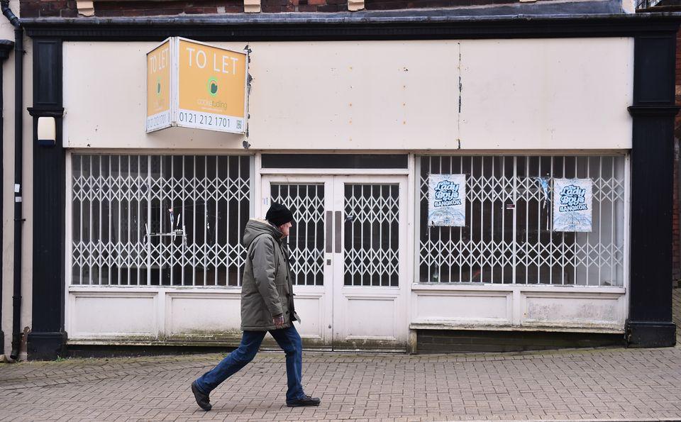 A man walks past an empty shop in
