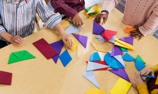 Cropped, high angle view of a multi-ethnic group of four children in kindergarten or first grade sitting...