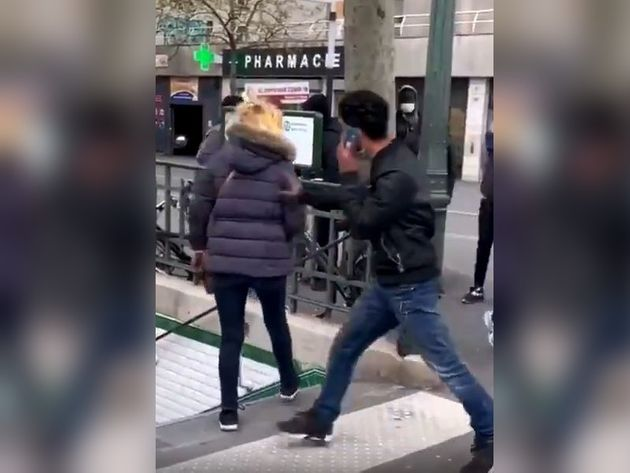 Un homme pousse une femme dans les escaliers du métro Porte de la