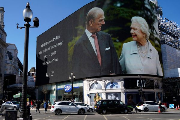 Images of the queen and the duke are displayed on screens at Piccadilly Circus in London while the funeral is held at Windsor