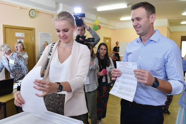 Russian opposition activist Alexei Navalny (R) looks on as his daughter Daria casts her vote at a polling...