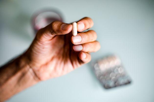 Close up of unrecognizable man taking meds/ supplements /