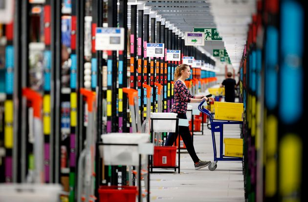 A 'picker' worker collects items from storage shelves as she collates a customer order inside an Amazon.co.uk fulfillment centre in Hemel Hempstead, north of London, in 2015