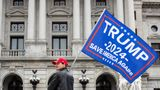 HARRISBURG, PENNSYLVANIA, UNITED STATES - 2021/02/27: A protester holds a Trump 2024 flag in front of the Pennsylvania State Capitol. About 40 people gathered on the steps of the Pennsylvania State Capitol for the '1st Amendment--Conservatives Being Censored' rally. (Photo by Paul Weaver/SOPA Images/LightRocket via Getty Images)