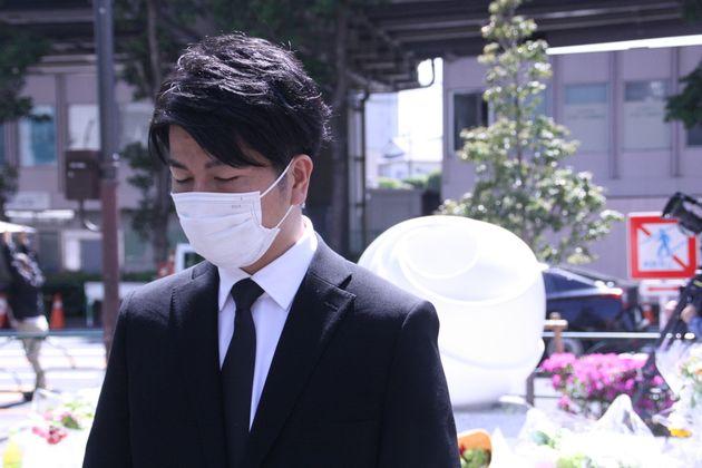 慰霊碑の前で取材に応じる松永さん