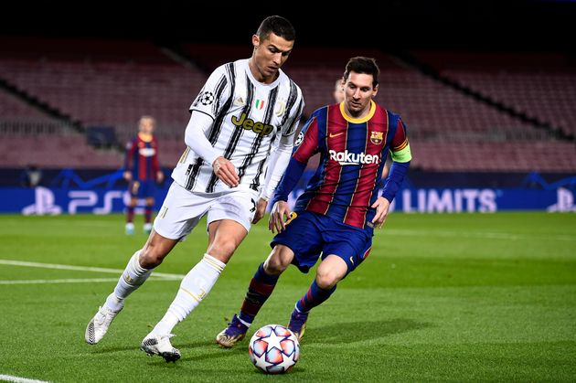 CAMP NOU, BARCELONA, SPAIN - 2020/12/08: Cristiano Ronaldo (L) of Juventus FC is challenged by Lionel...
