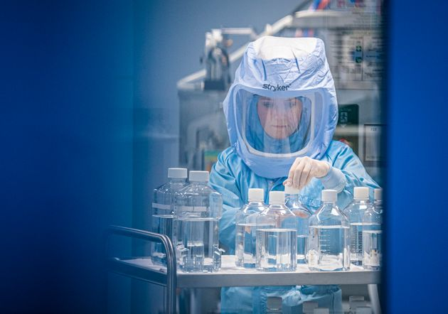 27 March 2021, Hessen, Marburg: Wearing full-body protective suits, laboratory assistants from the company...