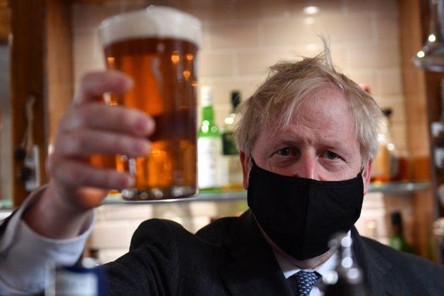 El prime ministro de Reino Unido, Boris Johnson, posa con una pinta de cerveza en la reapertura de los...