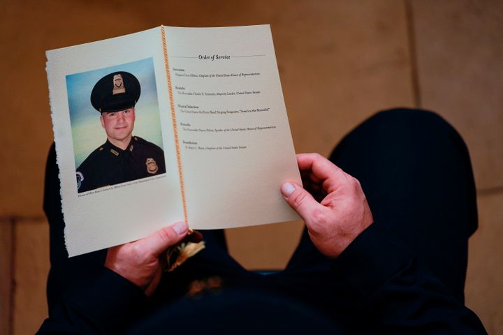 An officer holds a program as people pay their respects at the remains of U.S. Capitol Police officer Brian Sicknick.
