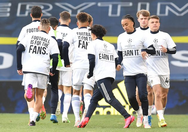 Players of Leeds United warm up while wearing protest t-shirts reading