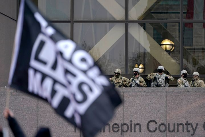 National Guard members are seen as a person flies a Black Lives Matter flag during a rally outside of the Hennepin County Gov