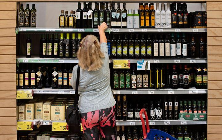 Mujer coge botella de aceite de oliva virgen extra de una estantería del supermercado.