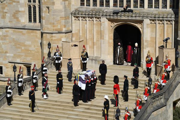 The Duke of Edinburgh's coffin, covered with his Personal Standard, arrives at St George's Chapel carried by a be