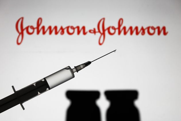 Medical syringe is seen with Johnson and Johnson company logo displayed on a screen in the background...