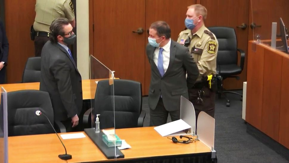 In this image from video, former Minneapolis police officer Derek Chauvin is taken into custody as his attorney, Eric Nelson,