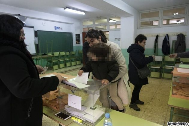 Una mujer vota con su hijo en un colegio de Madrid, en