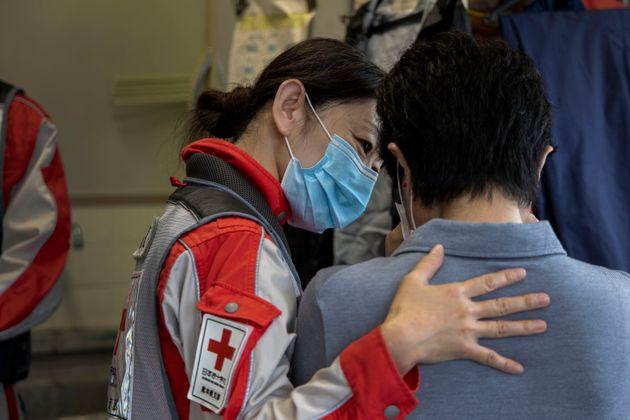 2020年7月6日。看護師の肩を借りて泣く地元役場の職員。被災者の支援者でありつつ、自身も避難生活を余儀なくされていた被災者でもあった