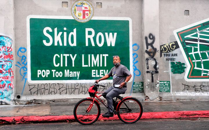 A cyclist rides past a Skid Row sign in Los Angeles on Feb. 1. A group of downtown businesses and residents sued local g