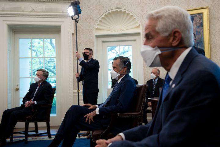 Sen. John Hickenlooper (D-Colo.), Senator Mitt Romney (R-Utah), Rep. Charlie Crist (D-Fla.), listen to President Joe Biden be