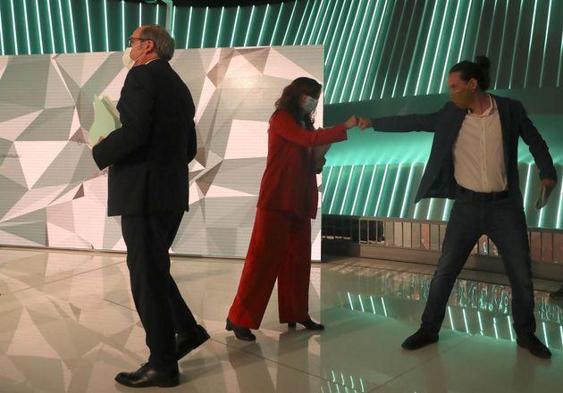 Mónica García (Más Madrid) y Pablo Iglesias (Podemos) se saludan tras el