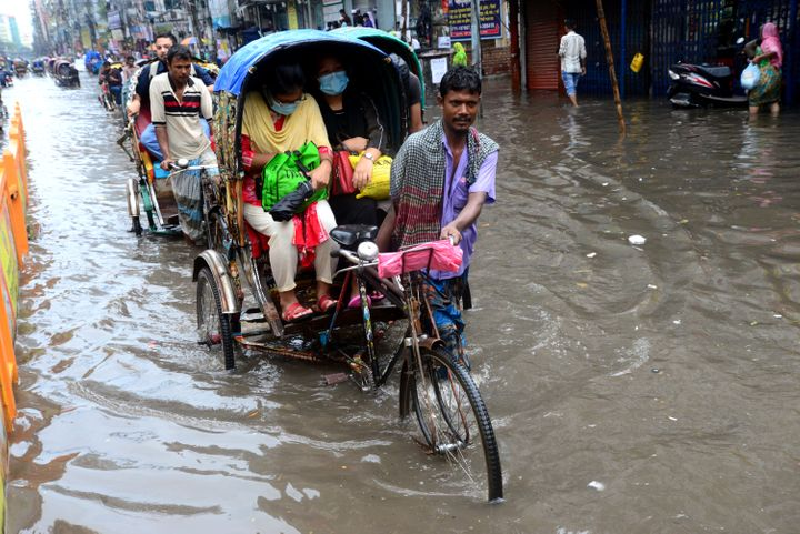 Vehicles and pedestrians slog through floodwaters in Dhaka streets in Bangladesh last October. Though Bangladesh has contribu