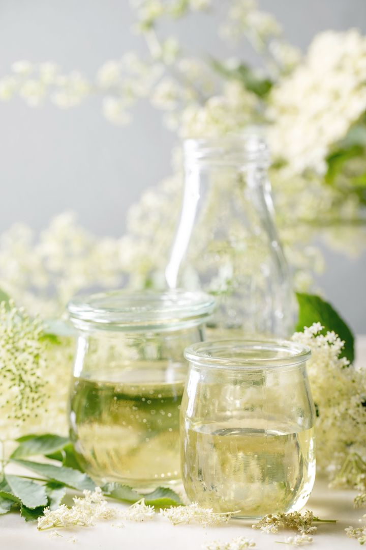 Elderberry flowers and leaves, glass jars of sweet homemade elderberry syrup on white marble table.
