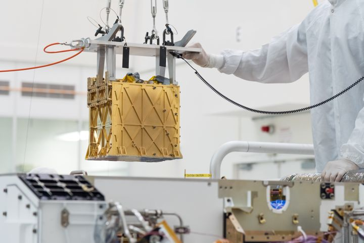 Technicians at NASA's Jet Propulsion Laboratory in La Cañada Flintridge, California, lower the Mars Oxygen In-Situ Res
