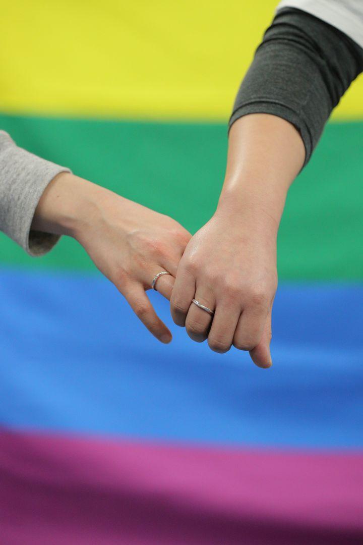 同性婚が認められないのは憲法に違反するとして損害賠償を求めた訴訟の判決後、記者会見を終えて手を取り合う原告=3月17日、札幌市中央区