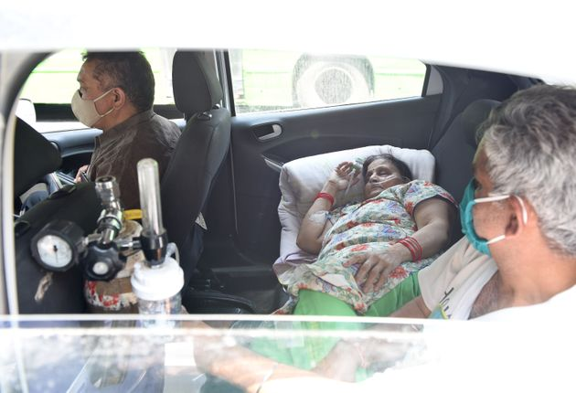 NEW DELHI, INDIA - APRIL 22: A Covid-19 patient on oxygen support waits inside a car for admission amid...