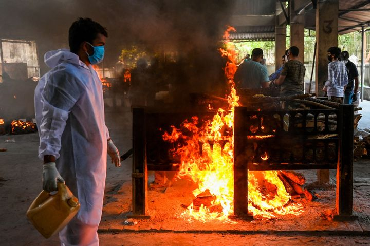 Crematorium staff light a pyre of a Covid-19 coronavirus victim, who died from a fire incident that killed 13 patients at the