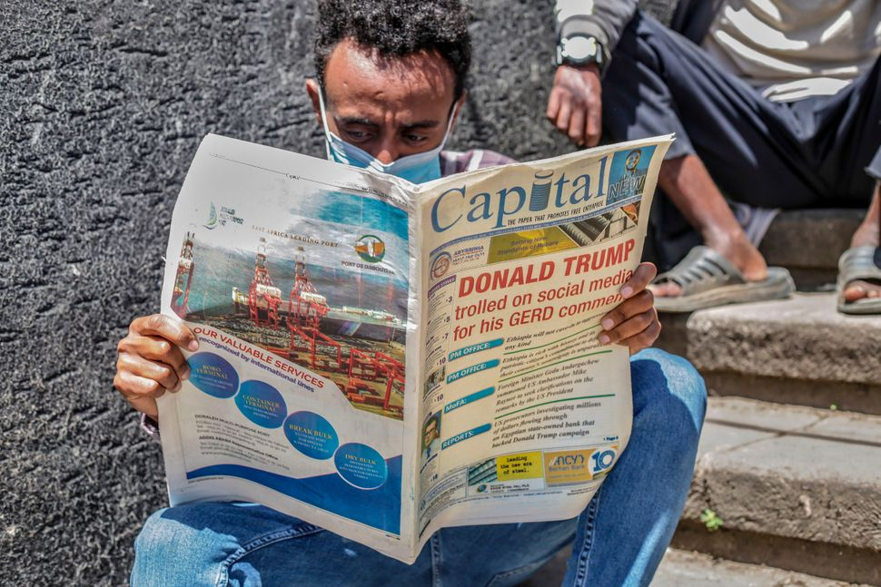A man sits in the street reading a copy of the Capital newspaper, an Ethiopian weekly business publication,...
