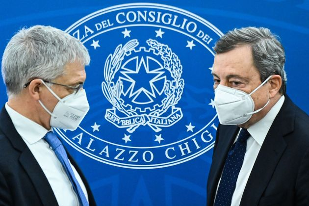Italy's Economy Minister, Daniele Franco (L) and Italy's Prime Minister, Mario Draghi stand after holding...