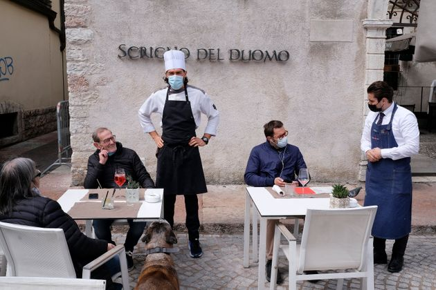 TRENTO, ITALY - APRIL 19: The people sitting at the outdoor tables of the restaurants finally eat together...