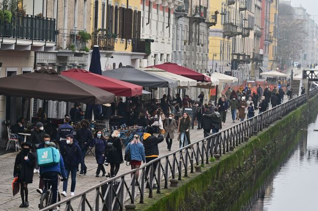 People enjoy bar and restaurant's terraces and stroll along the Naviglio canal in Milan on February 6,...
