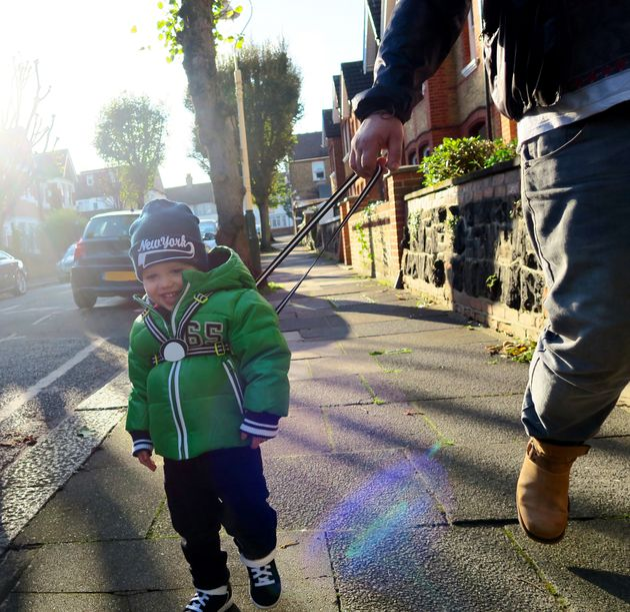 ハーネスをつけて保護者と歩く子供(イメージ)
