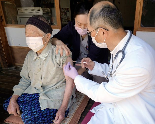 外出できないひとり暮らしの高齢者宅を訪れ、新型コロナウイルスのワクチンを注射する診療所の医師と看護師=4月21日、長野県南佐久郡北相木村
