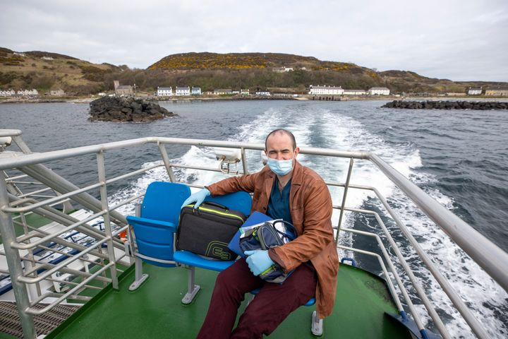 Dr Gavin Chestnutt travelling by boat to deliver a vaccine.