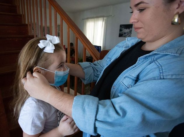 Une mère de famille enfile un masque à sa fille à Tenerife en Espagne le 26 avril...