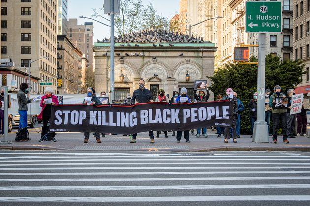 Un grupo de personas sostiene una pancarta que dice