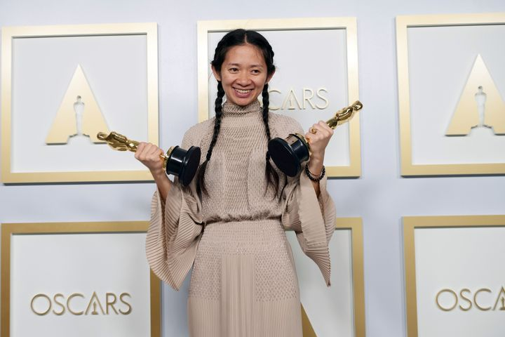 Chloé Zhao shows off both of her Oscars in the press room of the Academy Awards in Los Angeles.